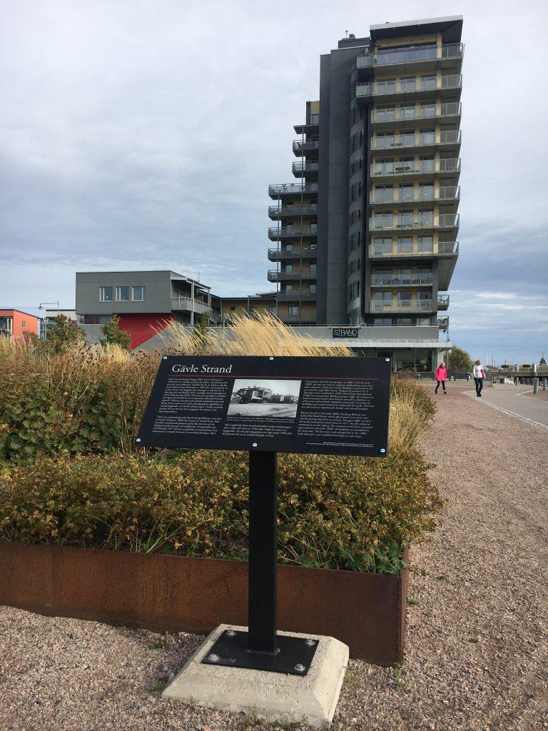 Kulturskylt märkt Gävle strand intill plantering vid grått höghus