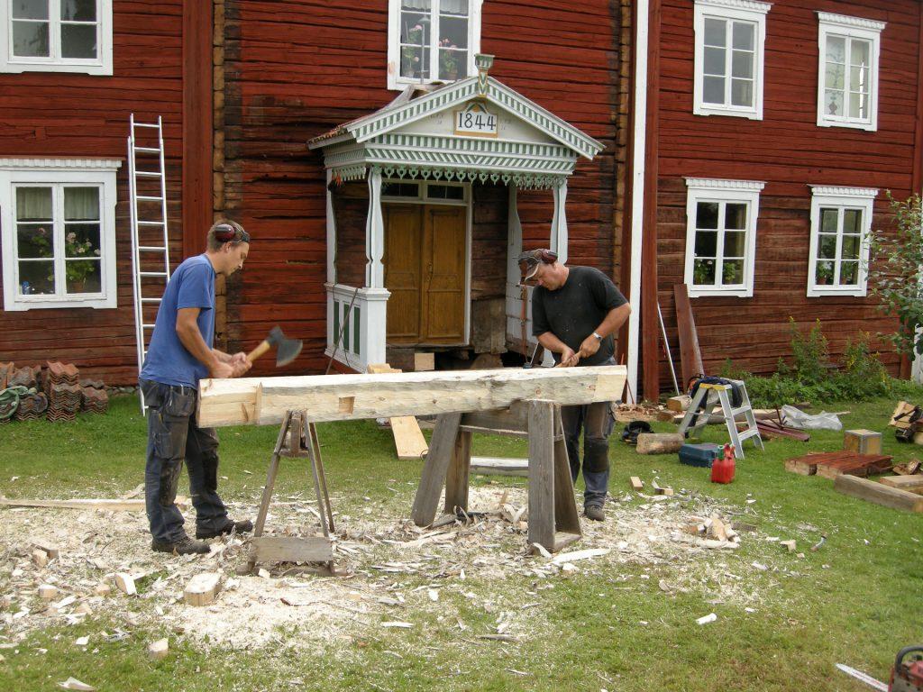män med verktyg hugger i trädbjälke utanför röd hälsingegård
