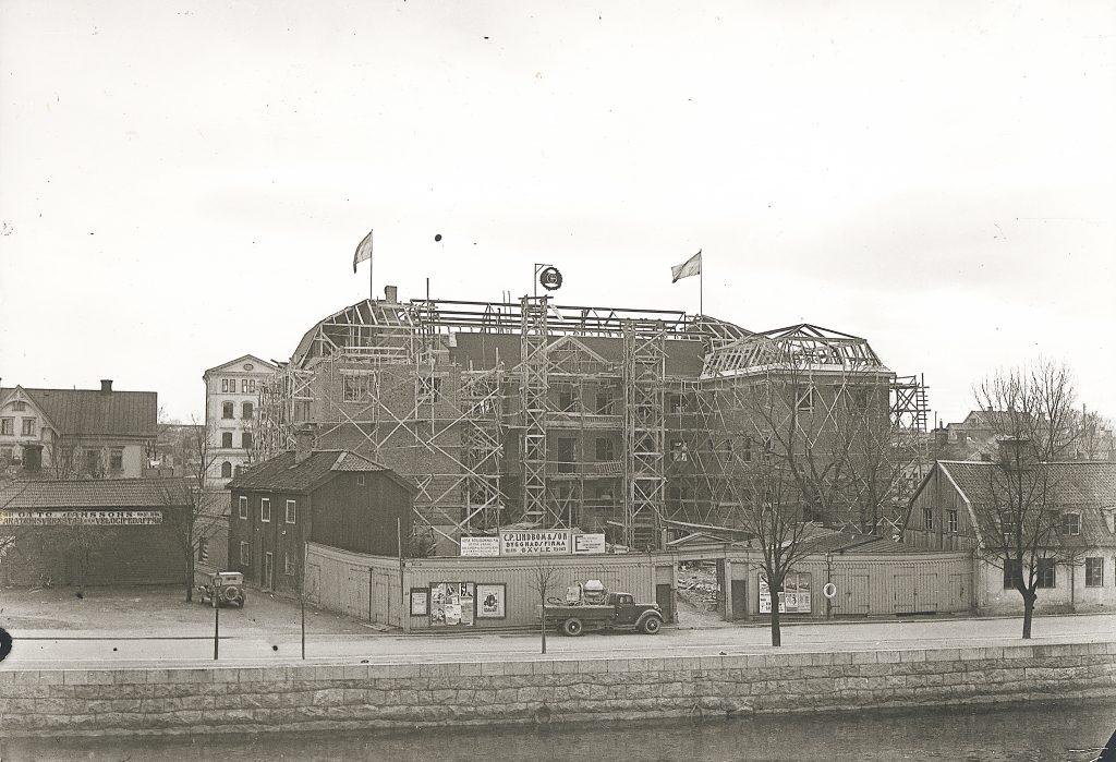 svartvit bild tegelbyggnad med byggställningar och flaggor på taket