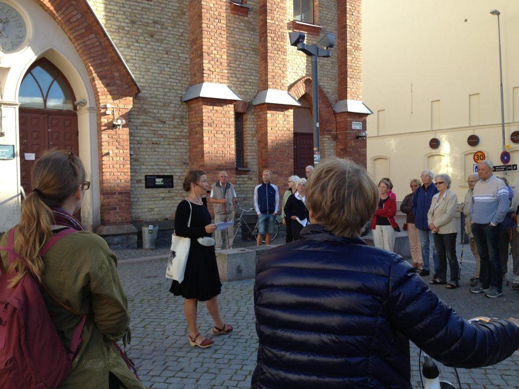 personer stående i halvcirkel runt guide vid skyltvandring
