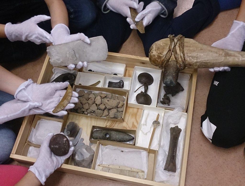 händer med tyghandskar håller i arkeologiska föremål
