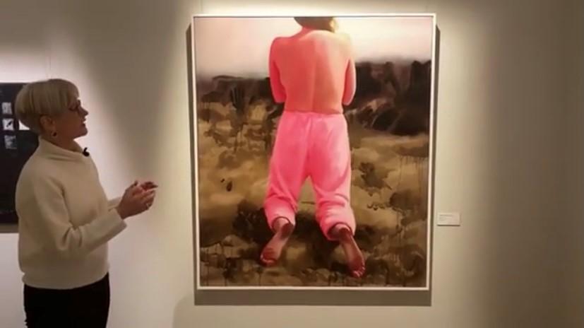 Kvinna visar en målning