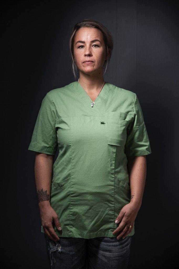 Porträttbild. Kvinna i gröna sjukhusarbetskläder mot mörk bakgrund.