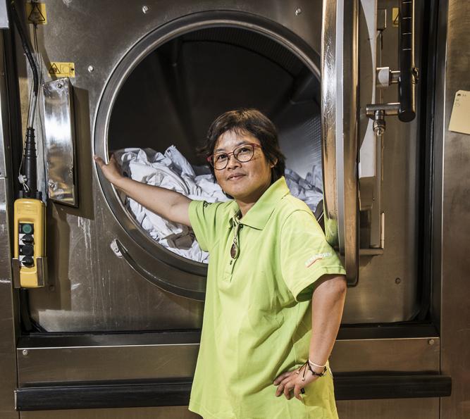 Kvinna i arbetskläder som står framför en stor tvättmaskin.