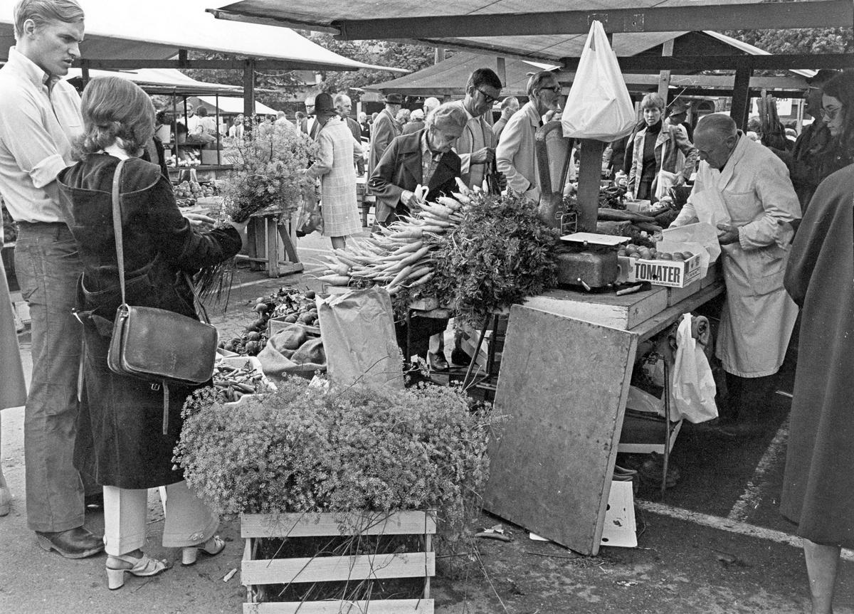 Torgstånd, grönsaker och människor