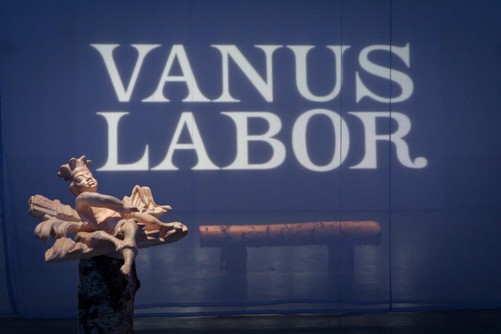 Projicerad text Vanus Labor med träskulptur framför.