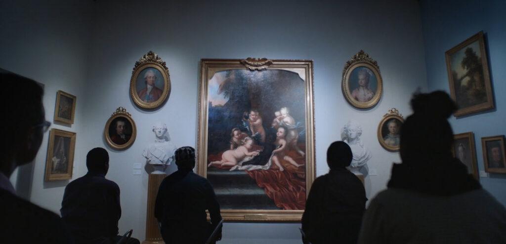 Människor tittar på äldre målning.