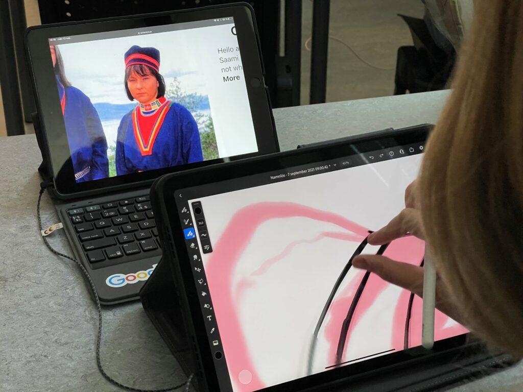 Två datorskärmar. På den ena syns en kvinna klädd i samisk dräkt. Den andra skärmen viisar ett motiv i rött och en hand som arbetar med motivet på skärmen.