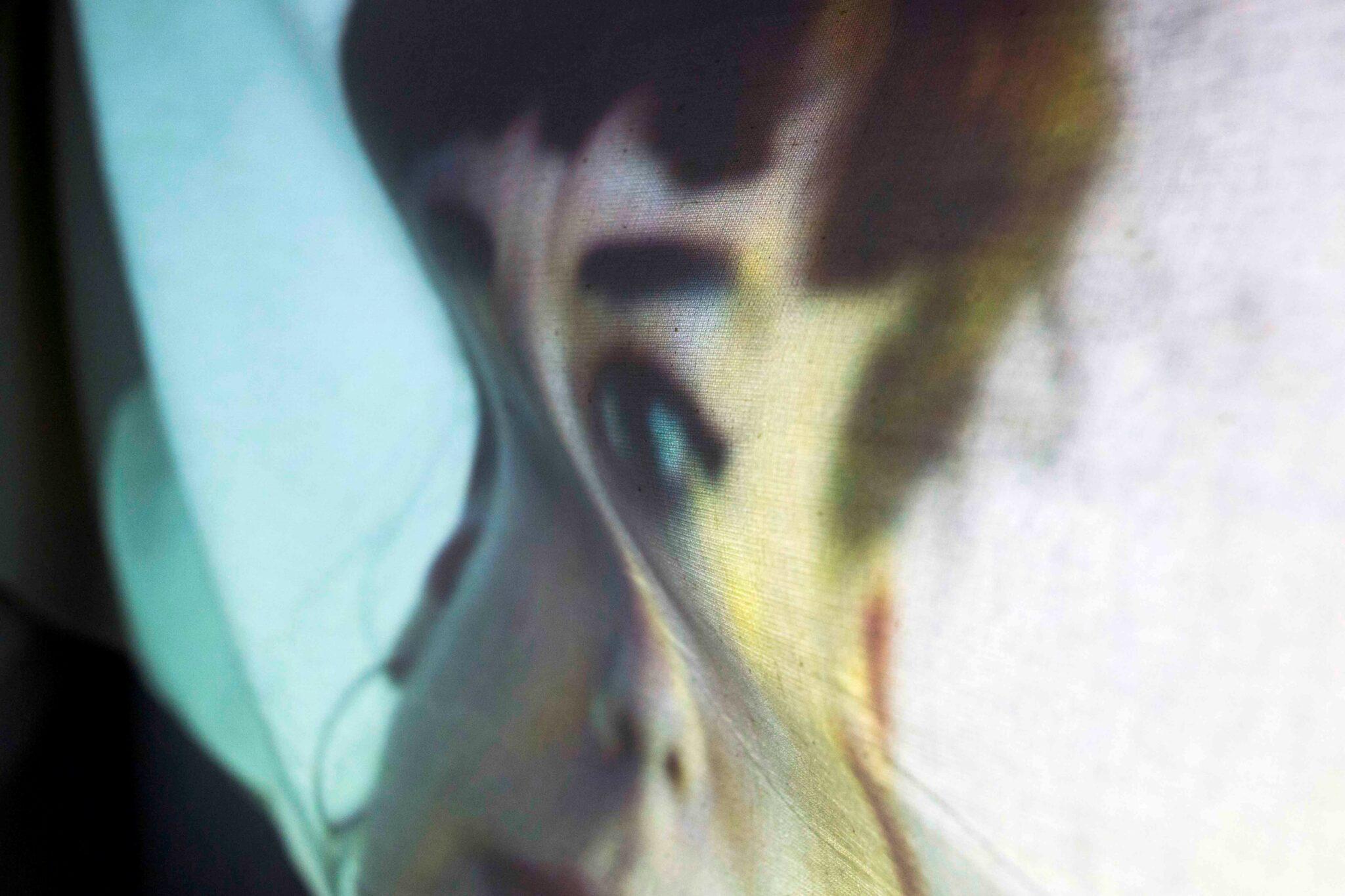 En projicerat ansikte på en knölig textil.